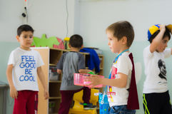 埃斯基谢希尔,土耳其- 2017年5月05日:有运载一个杯子的红色斗篷的甜小男孩在幼儿园教室 库存图片