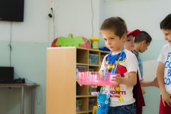 埃斯基谢希尔,土耳其- 2017年5月05日:有运载一个杯子的红色斗篷的甜小男孩在幼儿园教室 免版税库存图片
