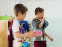 埃斯基谢希尔,土耳其- 2017年5月05日:有运载一个杯子的红色斗篷的甜小男孩在幼儿园教室 库存照片
