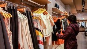 埃斯基谢希尔,土耳其- 2017年4月18日:看一件时兴的礼服的少妇在衣物商店在埃斯基谢希尔 库存图片