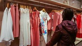 埃斯基谢希尔,土耳其- 2017年4月18日:看一件时兴的礼服的少妇在衣物商店在埃斯基谢希尔 免版税库存图片