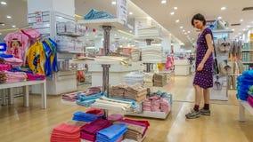 埃斯基谢希尔,土耳其- 2017年5月04日:美丽的深色的妇女审查的毛巾在一家商店在埃斯基谢希尔 库存照片