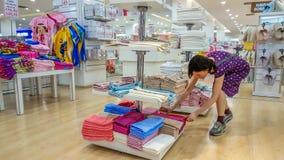埃斯基谢希尔,土耳其- 2017年5月04日:美丽的深色的妇女审查的毛巾在一家商店在埃斯基谢希尔 免版税库存图片