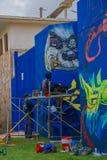 埃斯特角城,乌拉圭- 2016年5月06日:休息在绞刑台的年轻艺术家,当某些其他朋友继续绘墙壁时 免版税库存照片