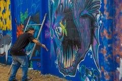 埃斯特角城,乌拉圭- 2016年5月06日:有一把刷子的未认出的年轻人在他的绘街道画的手上 免版税库存图片