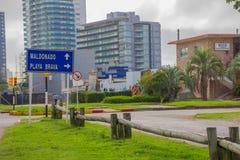埃斯特角城,乌拉圭- 2016年5月06日:表明方向的蓝色金属标志对在街道的海滩与一些楼a 图库摄影