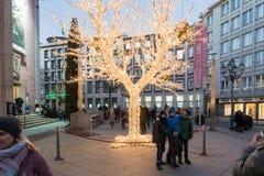 埃森,德国- 2016年12月04日:未认出的孩子为在一棵有启发性树前面的一张照片摆在 图库摄影