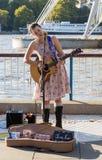 埃米莉唱歌与吉他的李泰晤士河 免版税图库摄影