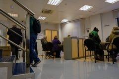 埃纳雷斯堡, 2018年1月5日:一个银行办公室的内部有现代家具和人坐的和站立的解决的proble 图库摄影