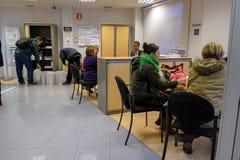 埃纳雷斯堡, 2018年1月5日:一个银行办公室的内部有现代家具和人坐的和站立的解决的proble 免版税库存照片