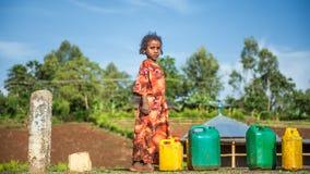 埃赛俄比亚的女孩向水求助在亚的斯亚贝巴,埃塞俄比亚附近 免版税图库摄影