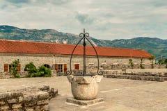 城堡在老镇在布德瓦,黑山 有一口古老井和一个美丽的大厦正方形的片段 免版税库存图片