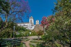 从城堡庭院的看法圣玛丽亚历史的教会的在城市Tavira,阿尔加威,葡萄牙做Castelo- 免版税库存图片
