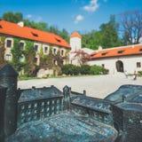 城堡的模型在有真正的大厦的Pieskowa Skala在背景,盲人识字系统系统中 库存照片