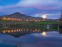 城市光、在池塘和山反映的上升的月亮 库存图片