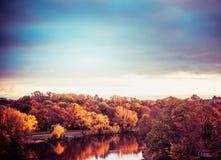 城市公园秋天风景有五颜六色的树、湖和天空的在日落 库存照片