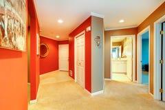 城市公寓的大红色走廊与开放卫生间门和米黄地毯。 库存照片