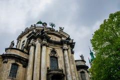 城市利沃夫州的古老建筑学 一个古老多米尼加共和国的教会和春雨的门面天空 免版税库存照片