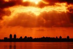城市剪影和红色天空与太阳发出光线 免版税库存照片