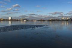 城市反射在微明的一个冻湖 库存图片