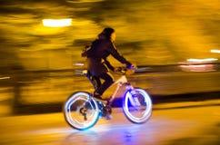 城市和一个骑自行车者的剪影的被弄脏的光有gl的 库存照片
