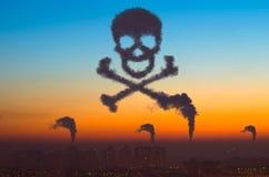 城市和工业烟云以一块头骨的形式天空日落有骨头的,大气污染的危险的标志和耳朵 免版税库存图片