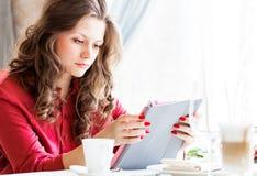 城市咖啡馆的美丽的妇女 她id饮用的咖啡和使用她的片剂 库存照片