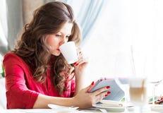 城市咖啡馆的美丽的妇女 她id饮用的咖啡和使用她的片剂 免版税库存照片