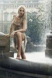 城市喷泉的性感的湿妇女在雨中 免版税图库摄影