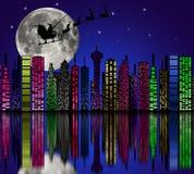 城市在晚上。在天空的圣诞老人。与圣诞节结婚 免版税库存照片