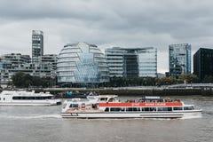 城市在泰晤士河,伦敦,背景的现代未来派看的办公室的巡航小船 库存图片