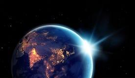 城市在行星地球的晚上点燃与与太阳上升 免版税库存照片
