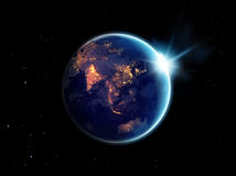 城市在行星地球的晚上点燃与与太阳上升 库存照片