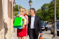 城市夫妇成熟漫步的购物 免版税库存图片
