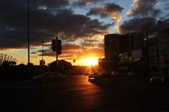 城市日落在与汽车的一阴天在交通信号juction 免版税库存照片