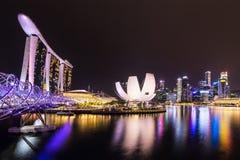 城市晚上新加坡地平线 螺旋桥梁,小游艇船坞海湾铺沙旅馆和商业区 免版税图库摄影