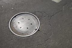 城市有老难看的东西人孔盖沥青柏油碎石地面的街道走道 免版税图库摄影