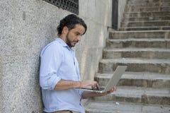 城市楼梯的拉丁人与看起来的便携式计算机一起使用满意和确信 免版税库存图片