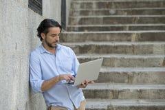 城市楼梯的拉丁人与看起来的便携式计算机一起使用满意和确信 库存照片