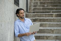 城市楼梯的拉丁人与看起来的便携式计算机一起使用满意和确信 免版税图库摄影