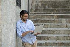 城市楼梯的拉丁人与看起来的便携式计算机一起使用满意和确信 库存图片
