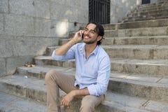 城市楼梯谈话的可爱的拉丁人愉快在看起来的手机满意和确信 库存照片