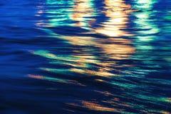 城市点燃反映 在水的五颜六色的强光 免版税库存照片