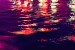 城市点燃反映 在水的五颜六色的强光 图库摄影