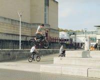 城市生活在布里斯托尔,在他的自行车的Tennager实践的把戏 库存图片