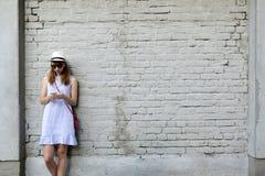 城市生活概念 站立在白色砖墙旁边的少妇听到在耳机的音乐 免版税库存图片