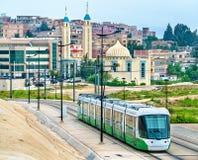 城市电车和一个清真寺在康斯坦丁,阿尔及利亚 库存照片