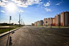城市的一个新的区的一个空的路交叉点在居民住房旁边的在反对多云天空的一个晴朗的晴天 库存图片