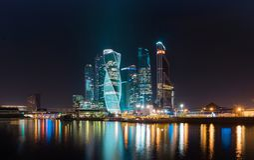城市的商业区在五颜六色的夜点燃 一个大城市莫斯科的午夜光在河被反射 免版税库存图片