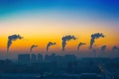 城市的工业风景的晚上视图有黑烟排放的从在日落的烟囱 免版税库存照片